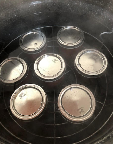 Filled jars added to boiling water canner
