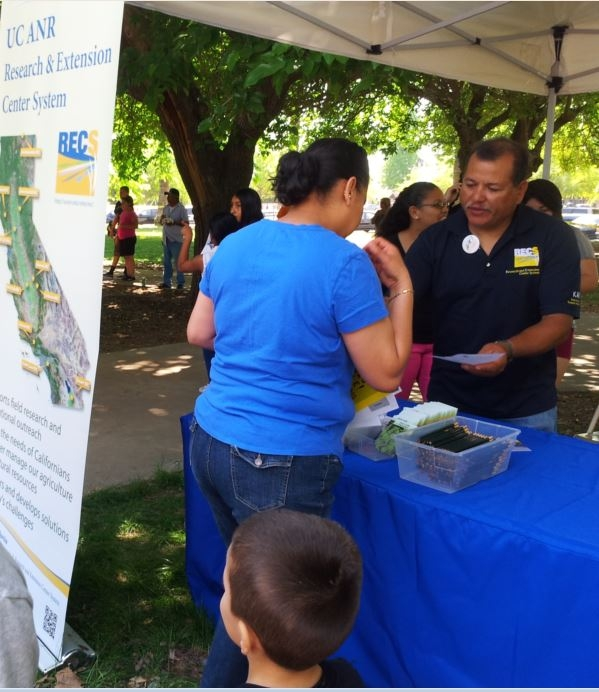 Rodolfo Cisneros sharing information about Kearney with a local resident at the 2014 Parlier Earth Day.