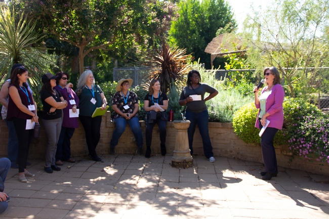 Judy McClure speaking in front of a group of people at the garden gate, with flowers and low water use plants in the background.