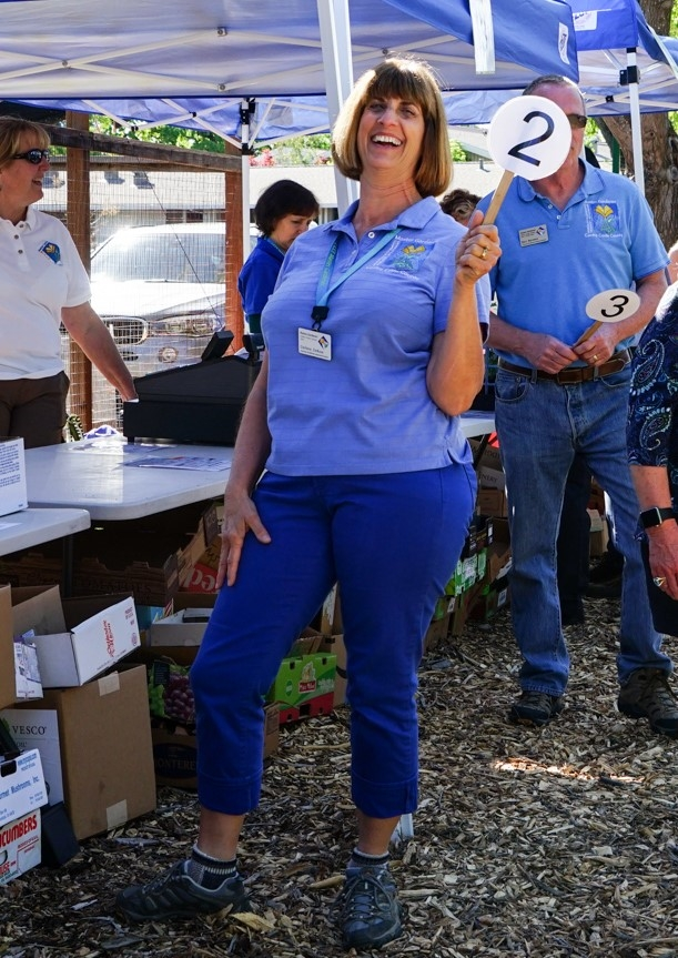 Darlene DeRose wearing her blue MG polo, blue jeans while holding up a number 2 sign in an outdoor educational display.