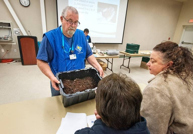 Ted Hawkins wearing a blue shirt, blue MG vest and MG lanyard around his neck while holding a black bin with worms and dirt while students look on.