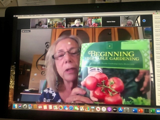 A Zoom meeting screenshot of Nancy Herz holding up a Beginning Vegetable Garden book with a hand holding a vine of red tomatoes.