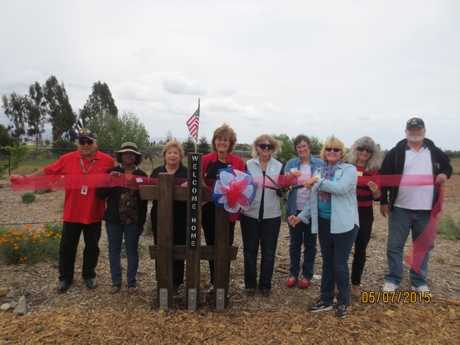 "Nine people stand on a wood chip covered garden path, behind a post, engraved vertically with the words welcome home."" A small American flag is mounted atop the post. One person holds garden shears, poised to cut through a translucent red ribbon being held by eight other gardeners."