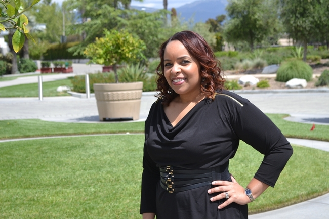 Elizabeth McSwain headshot image, McSwain is standing in front of a lush green garden in San Bernardino County.