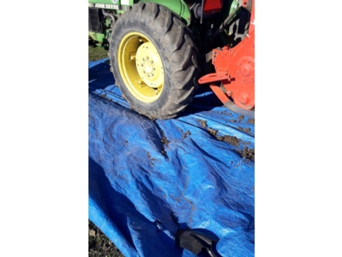 Soil brushed from tiller and tractor tires onto a plastic tarp.