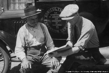 Farmer seeks assistance from UCCE farm advisor on the running board of a historic UC Cooperative Extension vehicle.