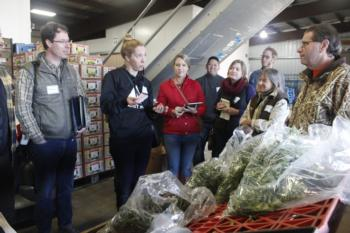 Napa County farmer Carolyn Kritikos, 2nd from left, asks Tony Leutza, far right, general manager of Washington Vegetable Co., about buyer requirement