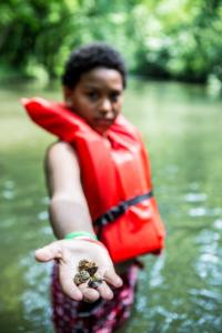 A 4-H youth explores a local river.