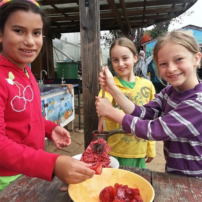 Niños preparando un plato con frutas frescas en los jardines Life lab en UC Santa Cruz. Foto: Life lab