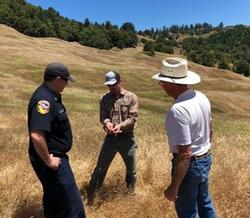 UCCE Advisor speaking to CAL FIRE and a landowner about the benefits of prescribed fire.