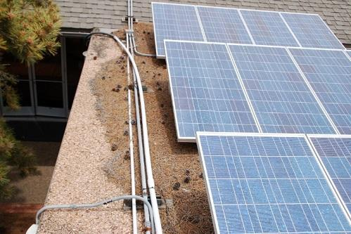 Solar panels installed on a flat roof with accumulated debris